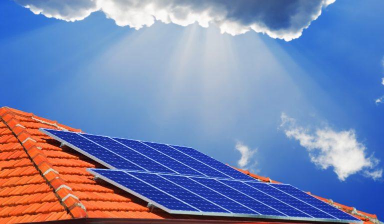 l'immagine ricorda una nuova era nel mercato fotovoltaico grazie al credito di imposta. Si vede il sole dietro le nuvole che illumina i pannelli solari su un tetto di una casa.
